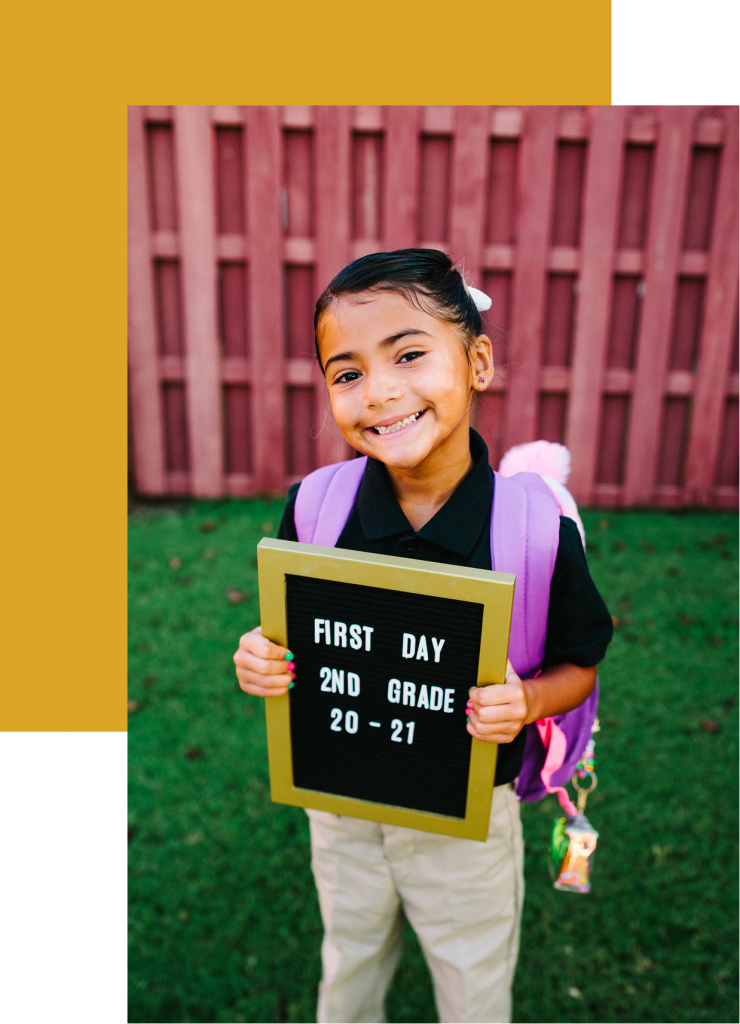 a student holding a sign for her first day of school